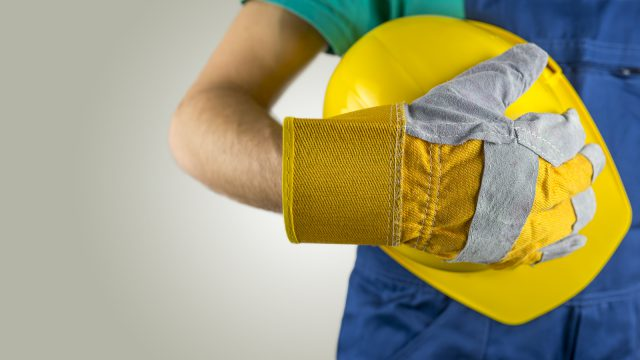 Workman wearing a protective glove holding a yellow hardhat or safety helmet conceptual of a builder construction worker tradesman or manual labourer