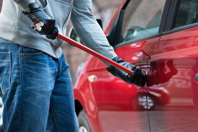 Close-up Of Thief Opening Car's Door With Crowbar