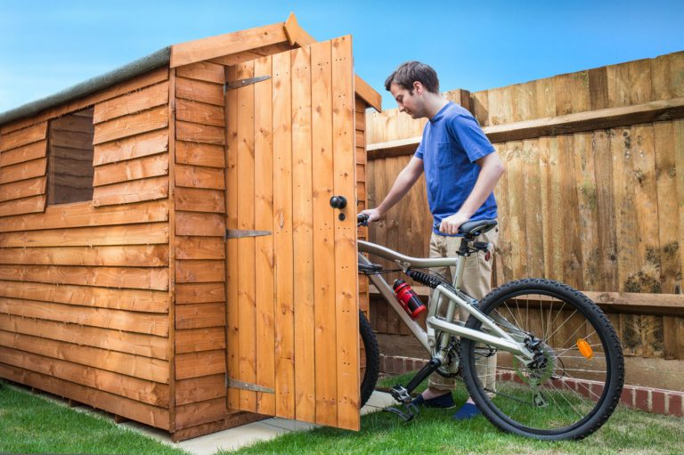 Man putting bike into secure shed